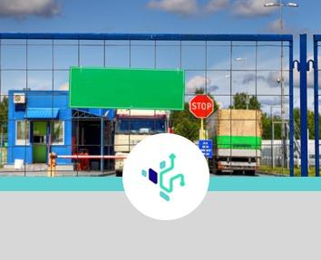 grafika z logo firmy oraz widoczne przez siatkę ciężarówki, stojące na bramkach ochrony widoczne