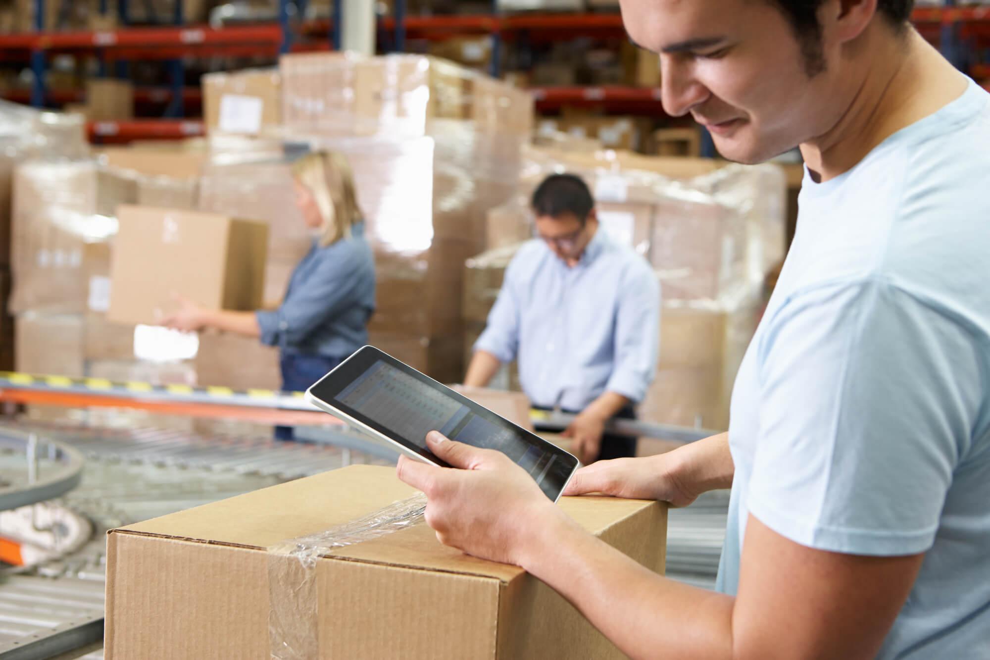 Pracownik korzysta z tabletu w punkcie dystrybucji magazynu